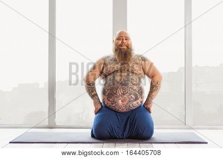 Happy middle-aged male fatso is resting after exercise. He is sitting on sporty carpet near window and smiling