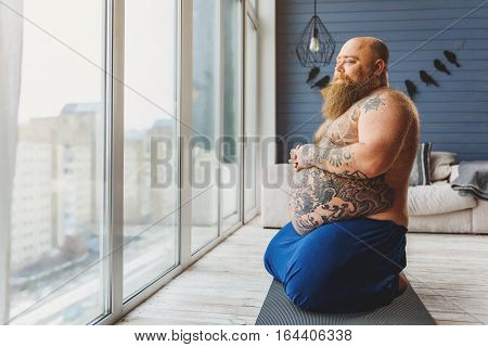 Calm fat man is relaxing after exercising at home. He is sitting on mat and looking through window pensively