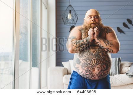 Shocked fat man is staring at camera with surprise. He is touching his beard. Guy has large belly with tattoo