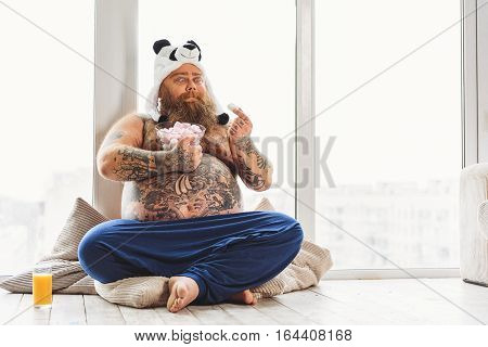 Bearded fat man is looking at zephyr with desire. He is sitting on floor near window. Guy is wearing funny hat