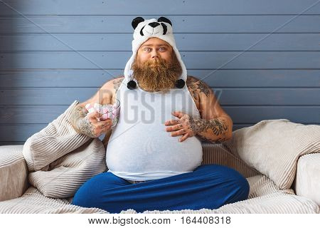 Carefree male heavy eater is holding zephyr and touching his large belly with satisfaction. He is looking at camera and smiling. Man is sitting on couch at home