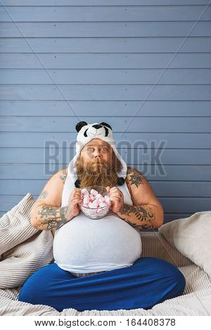 This is my favorite food. Greedy fat man is showing bowl of zephyrs. He is sitting on sofa and staring at camera with desire