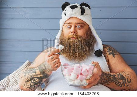Funny fat man is staring at sweet food with desire. He is sitting on sofa with relaxation