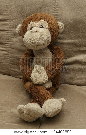 a stuffed toy monkey sitting looking happy