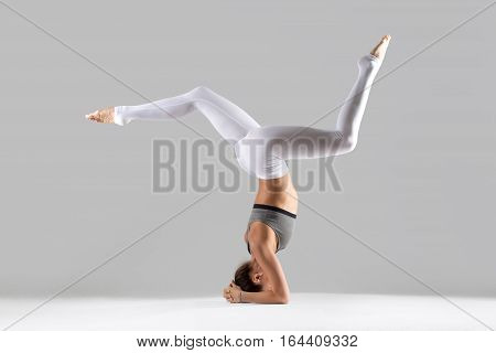 Young attractive woman practicing yoga, standing in headstand exercise, salamba sirsasana pose, working out wearing sportswear, white pants, indoor full length, isolated against grey studio background