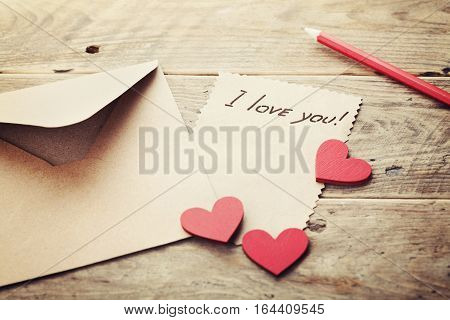 Envelope or letter, red hearts and notes I love you on vintage wooden table for Valentines Day in retro toning.