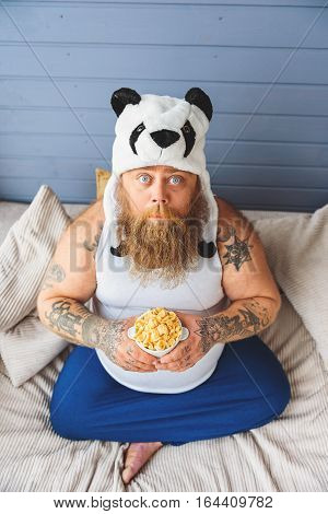 Is that all food. Upset thick guy is on a diet. He is holding cornflakes and looking up with hope. Top view