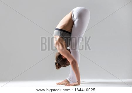 Young attractive woman practicing yoga, standing forward bend, head to knees exercise, uttanasana pose, working out wearing sportswear, indoor full length, isolated, grey studio background