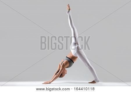 Young attractive woman practicing yoga, standing in one legged downward facing dog exercise, eka pada adho mukha svanasana pose, wearing sportswear, indoor full length, isolated, grey background