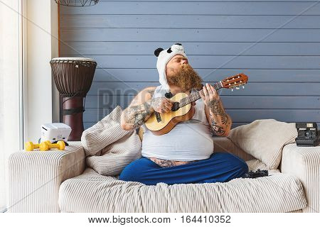 Cheerful male fatso is playing small guitar at home. His eyes are closed with pleasure