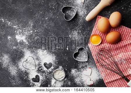Baking background with flour, rolling pin, eggs and heart shape on dark kitchen table top view for Valentines day cooking. Flat lay style.