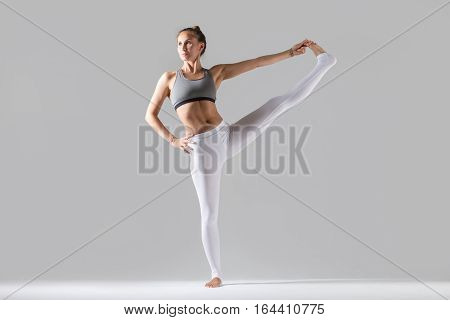 Young attractive woman practicing yoga, standing in Extended Hand to Big Toe exercise, Utthita Hasta Padangustasana pose, working out wearing sportswear, indoor full length, grey studio background