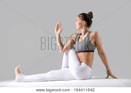 Young attractive woman practicing yoga, sitting in Half lord of the fishes exercise, Ardha Matsyendrasana pose, working out wearing sportswear, indoor full length, isolated, grey studio background