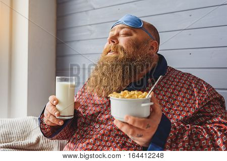This is the best breakfast ever. Joyful fat man is enjoying healthy food and smiling. He is holding bowl of cornflakes and glass of milk. His eyes are closed with enjoyment