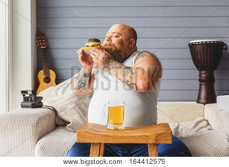 Happy heavy eater is smelling sandwich with enjoyment. He is sitting on sofa near glass of beer and smiling