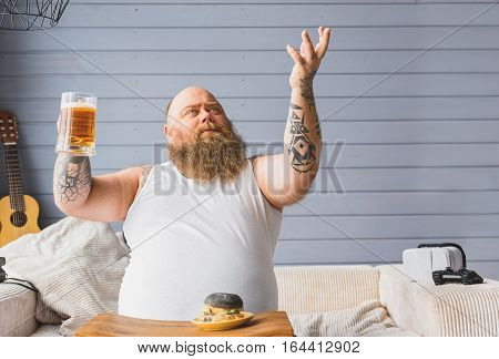 This is beverage of Gods. Confident fat man is holding glass of beer and stretching arm up with glad. He is sitting on couch at home