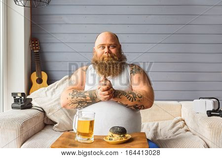I am ready to eat. Cheerful fat man is rubbing his hands while sitting near beer and sandwich. He is looking at camera and smiling