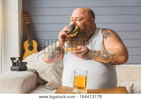 Hungry thick man is biting sandwich with greed. He is sitting on sofa near beer
