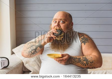 Starving male heavy eater is biting sandwich with greed. He is staring at camera while sitting sofa