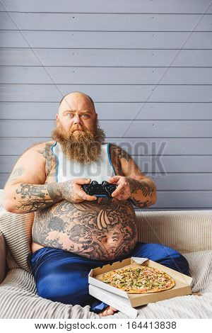I lost this game. Sad fat guy is holding joystick and looking at camera with frustration. He is sitting in living room and eating junk food