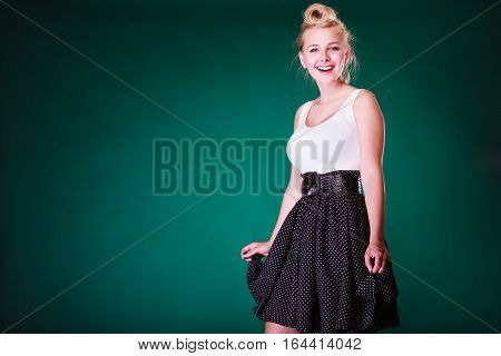 Fashion clothing disguise concept. Lovely young pin up girl in vintage hairstyle wearing retro black and white dress with big belt. Studio shot on green background