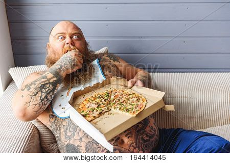 Hungry fat man is biting pizza with greed. He is sitting on sofa and looking forward with aggression