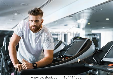 Happy man is standing in gymnasium, he inclining at treadmill