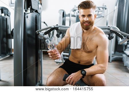 Confident half-naked guy is sitting on power training apparatus. He looking at camera with smile and holding bottle of water