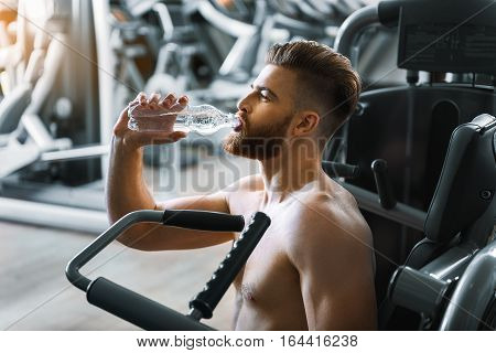 Tired guy is sitting in room at power training apparatus and drinking water
