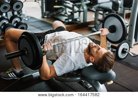 Strong bearded sportsman is lying at sportive bench. He lifting heavy barbell