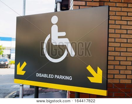 Disabled parking space sign and symbols on a pole warning motorists