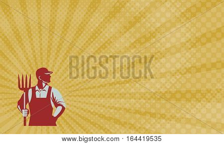 Business card showing Illustration of organic farmer holding pitchfork looking to the side with one hand in pocket viewed from front set on isolated white background done in retro style.