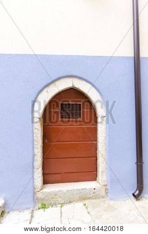 Traditional picturesque Mediterranean architecture at medieval town Vrbnik on Krk island Croatia. View of arched wooden door blue wall and inclined narrow alley.