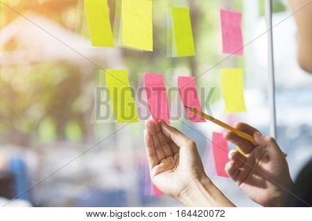 business people having a meeting in office business people post it notes in glass wall soft focus