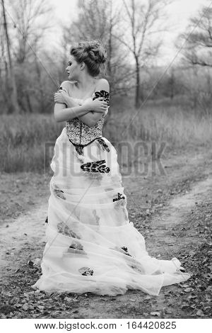 Beautiful young lady in gorgeous vintage white dress in the forest. Late autumn cold. Melancholy. Black and white