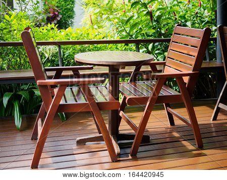 Outdoor Patio Furniture set of brown wooden, green tree background in garden