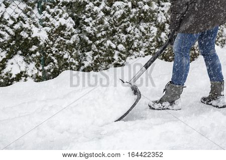 Woman shoveling snow on pavement in town