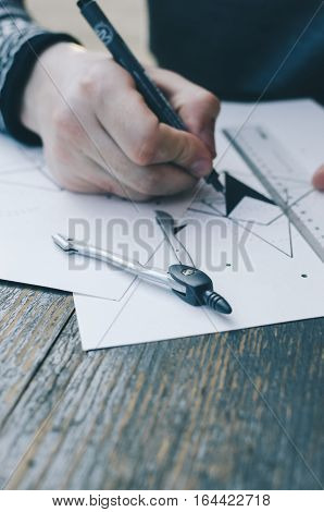 Man drawing a sketch on the white papper