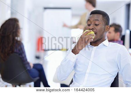 Closeup portrait serious business man, deal maker eating green apple Human face expression, corporate executive emotion