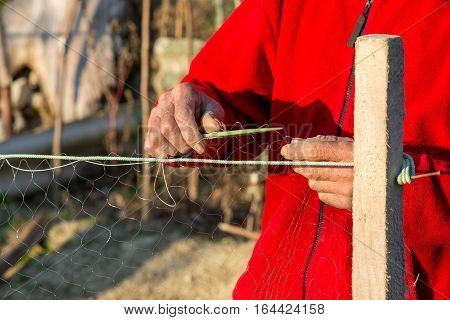fisherman knits fishing nets - - selective focus copy space