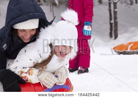 Happy mother and daughter laughing and rolling with snow hill. Winter fun.
