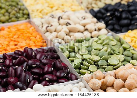Pulses food background assortment - legume kidney beans peas lentils in square cells macro. Healthy protein food.