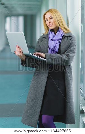 Portrait of blond businesswoman working on laptop in lobby.