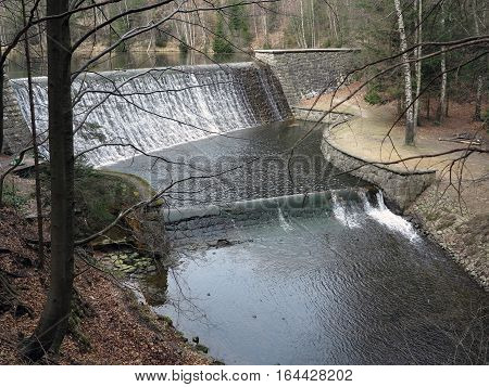Cascade of water to spillway of the dam in the forest