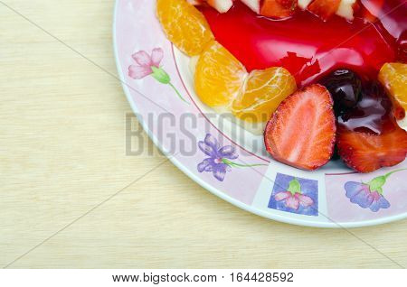 Strawberry jelly dessert flavored with half piece of strawberry berry and orange on the flower pattern dish top view with blank copy text space on wood background