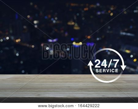 24 hours service icon on wooden table over blur colourful night light city tower background Full time service concept