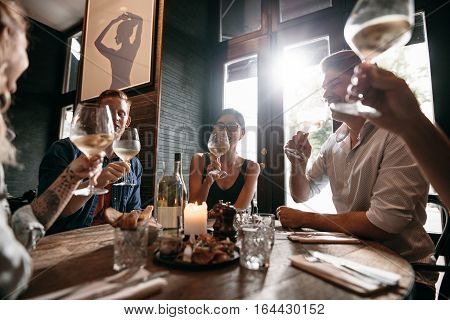Diverse group of young people having wine at restaurant. Men and women meeting at a restaurant for dinner.