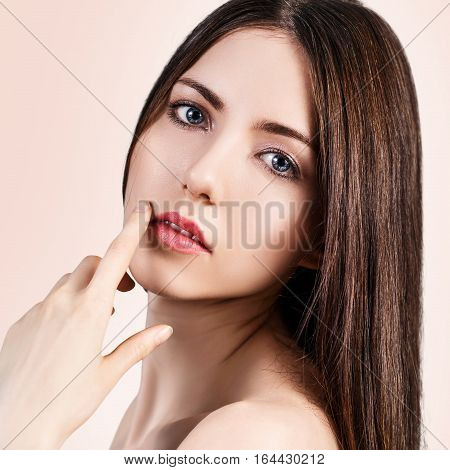 Young beautiful woman with healty fresh skin over beige background. Spa concept.