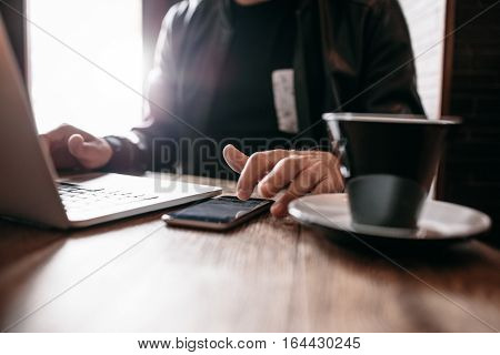 Close up shot of man sitting at cafe with laptop using mobile phone. Hands of man using smart phone at coffee shop