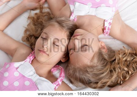 Portrait of a two sisters twins sleeping together